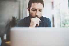 Skäggig affärsman som arbetar på det moderna vindkontoret Eftertänksamt mansammanträde och använda den moderna bärbara datorn sud Arkivfoto