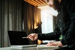 Skäggig affärsmanshowpenna på bärbar datorskärmen Den unga entreprenören framlägger affärsplan, visar information, jämför data Royaltyfri Fotografi