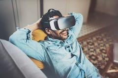 Skäggig afrikansk man som tycker om virtuell verklighetexponeringsglashörlurar med mikrofon eller anblickar 3d, medan koppla av p Arkivbild