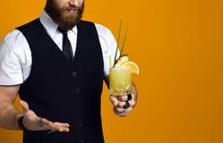 Skäggig bartender med skägginnehavcoctailen i waistcoat royaltyfria bilder