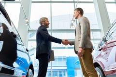 Skäggig chef Selling Cars i visningslokal royaltyfri fotografi