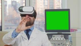 Skäggig doktor som bär exponeringsglas för vr 3d, dator med den gröna skärmen på baksidan stock video