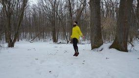 Skäggig färdig man som hoppar over med det hoppa repet i vinterskog med fritt utrymme stock video