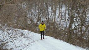 Skäggig färdig manlig jogger som upp kör kullen i vinterskog arkivfilmer