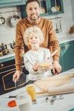 Skäggig fader och lockigt sonanseende i modernt rymligt kök royaltyfri fotografi