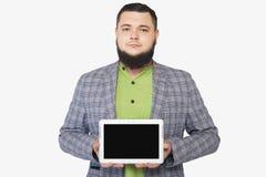 Skäggig fet man som rymmer en mobil enhet Fotografering för Bildbyråer
