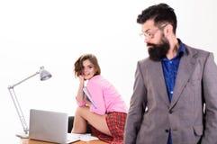 Skäggig framstickandeställning för man framme av den arbetande bärbara datorn för sexig flicka Kontorschef eller sekreterare Sexi arkivbild