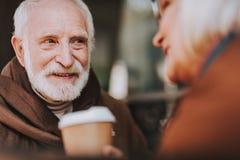 Skäggig gamal man som spenderar tid med frun på det utomhus- kafét royaltyfria bilder