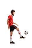 Skäggig grabb i en röd ärmlös tröja som jonglerar en fotboll Arkivfoto