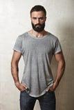 Skäggig grabb som bär den gråa t-skjortan arkivfoton