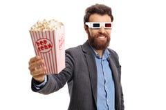 Skäggig grabb som bär exponeringsglas 3D och ger popcorn Royaltyfri Fotografi