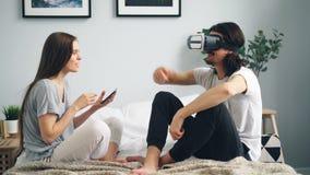 Skäggig grabb som hemma använder ar-exponeringsglas i säng medan skärm för tryckande på minnestavla för flicka arkivfilmer