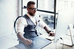 Skäggig grafisk formgivare Working Digital Tablet som drar den Wood tabellen för skrivbords- dator exponeringsglas man stilfullt  royaltyfri fotografi