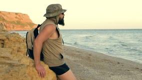 Skäggig handelsresande som ser till strandhimlen som tycker om solnedgång på havet - sommar och loppbegrepp lager videofilmer