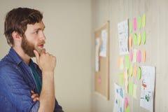 Skäggig hipster som ser kläckning av ideerväggen Arkivfoto