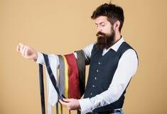 Skäggig hipsterhåll för man få slipsar Grabb med skägget som väljer slipsen Perfekt slips Valt band som har färger av arkivfoto