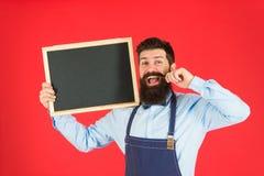 Skäggig hipsterkock V?lkommen Restaurang- eller kaf?annonsering Stor kokkonst Matlagning vid recept lycklig mankock med arkivfoto
