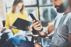 Skäggig Hipsterman som använder den moderna Smartphone handen Samlat Yound affärsfolk diskutera tillsammans den idérika idéstaden Arkivfoto