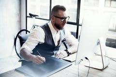Skäggig idérik tabell för skrivbords- dator för formgivareWorking Drawing Digital minnestavla Wood exponeringsglas man stilfullt  arkivbild
