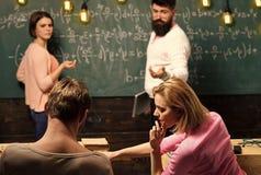 Skäggig lärare, föreläsare, hållande ögonen på studenter för professor under provet, examen, kurs Studenter gruppkompisar tala so arkivfoton