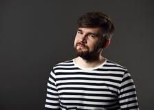 Skäggig le emotionell man i tillfällig randig t-skjorta på grå färger Arkivbild