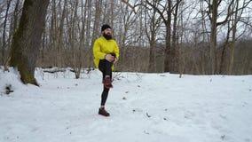 Skäggig man i det gula laget som sträcker ben i vinterskog med fritt utrymme arkivfilmer