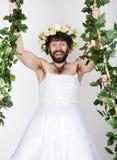 Skäggig man i en kvinnas bröllopsklänning på hennes nakna kropp som klamra sig fast intill vinrankan grimacing och roligt på hans Royaltyfri Foto