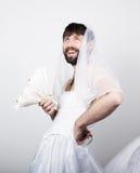 Skäggig man i en kvinnas bröllopsklänning på hennes nakna kropp som rymmer en blomma på hans huvud en skyla rolig skäggig brud Fotografering för Bildbyråer
