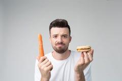 Skäggig man i en vit skjorta på en ljus bakgrund som rymmer en hamburgare och en morot Arkivfoton
