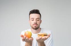 Skäggig man i en vit skjorta på en ljus bakgrund som rymmer en hamburgare och ett äpple Royaltyfria Bilder