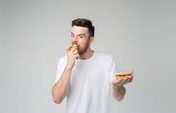 Skäggig man i en vit skjorta på en ljus bakgrund som rymmer en hamburgare och ett äpple Arkivbild