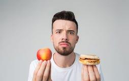 Skäggig man i en vit skjorta på en ljus bakgrund som rymmer en hamburgare och ett äpple Royaltyfri Fotografi