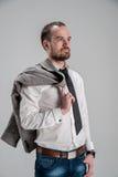 Skäggig man i en vit skjorta som rymmer ett omslag i H Royaltyfri Foto