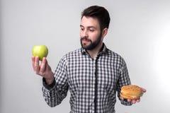 Skäggig man i rutig skjorta på en ljus bakgrund som rymmer en hamburgare och ett äpple Grabben gör valet mellan snabbt Royaltyfri Foto