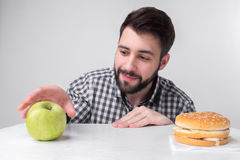 Skäggig man i rutig skjorta på en ljus bakgrund som rymmer en hamburgare och ett äpple Grabben gör valet mellan snabbt Arkivfoto