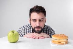 Skäggig man i rutig skjorta på en ljus bakgrund som rymmer en hamburgare och ett äpple Grabben gör valet mellan snabbt Royaltyfri Bild