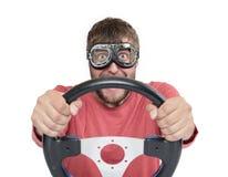 Skäggig man i stilfull skyddsglasögon med styrninghjulet som isoleras på vit bakgrund, begrepp för bilchaufför arkivbild