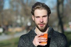 Skäggig man med den takeaway drinken på ny luft Parkerar den disponibla kaffekoppen för den macho hållen i soligt Kaffe- eller te fotografering för bildbyråer