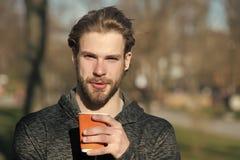 Skäggig man med den takeaway drinken på ny luft Parkerar den disponibla kaffekoppen för den macho hållen i soligt Kaffe- eller te royaltyfri fotografi