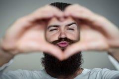 Skäggig man med händer i hjärtaform arkivbild