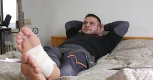 Skäggig man med sårat benfullföljande genom att använda hans bärbar dator och start som tänker i sovrummet arkivfilmer