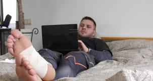 Skäggig man med sårat benfullföljande genom att använda hans bärbar dator och start som tänker i sovrummet lager videofilmer