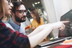 Skäggig man och kvinna som diskuterar marknadsföringsplan Produktmöte Start i öppet utrymmekontor arkivfoton