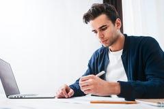 Skäggig man som använder bärbara datorn och förbereder projektplanet som sitter på tabellen hans moderna hem arkivbild