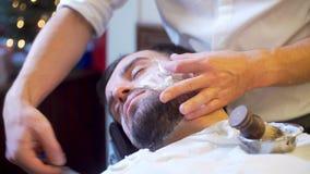 Skäggig man som får skäggfrisyr och rakar lager videofilmer