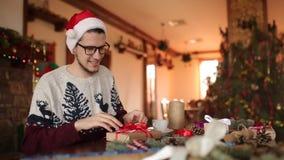 Skäggig man som hemma sitter och binder en pilbåge på gåvor för nytt år nära granträd För julhatt för grabb bärande inpackning arkivfilmer