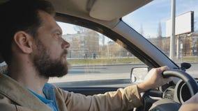 Skäggig man som kör en bil på en solig dag i staden arkivfilmer