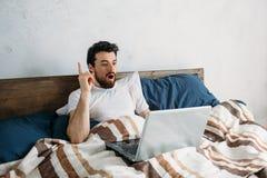 Skäggig man som ligger i morgonsäng med bärbara datorn Royaltyfri Bild