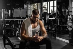 _ Skäggig man som sitter på bänk på idrottshallen med flaskan av vatten som ner som ser är trött royaltyfria foton