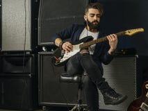 Skäggig man som spelar en elektrisk gitarr i en studio arkivbild
